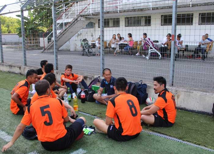 I giocatori tibetani in un momento di break. Fuori dal campo alle loro spalle, i supporters