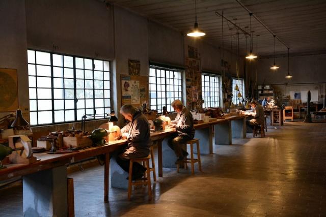 La bottega artigiana con le calde luci che illuminano le postazioni di lavoro