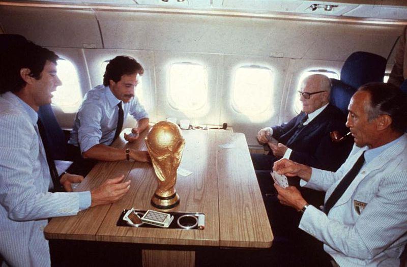 La partita a carte tra Pertini, Bearzot, Zoff e Causio al ritorno in Italia dopo la vittoria ai Mondiali. Sul tavolo, la Coppa del Mondo.