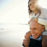 Grandfather at the Beach with Grand Daughter on his Shoulders --- Image by © Tim Hale Photography/Corbis